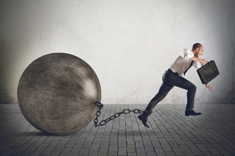 businessman running with ball and chain on ankle معاني